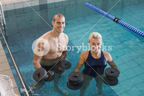 Swimmers working out with foam dumbbells in swimming pool at leisure centre