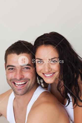 Blissful man with his girlfriend siiting on the bed