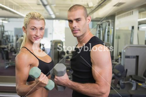 Couple exercising with dumbbells in gym