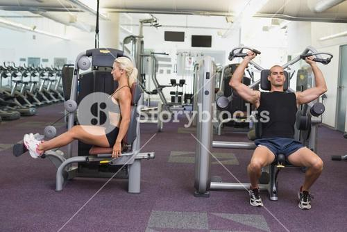 Fit couple using fitness machines at gym