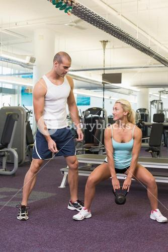 Trainer assisting woman with kettle bell in gym