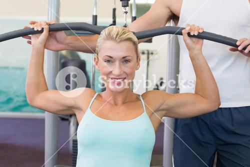 Beautiful woman exercising on a lat machine in gym