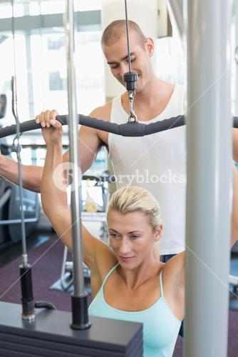 Male trainer assisting woman on lat machine in gym