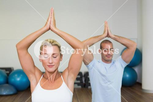 Couple with joined hands and eyes closed at fitness studio