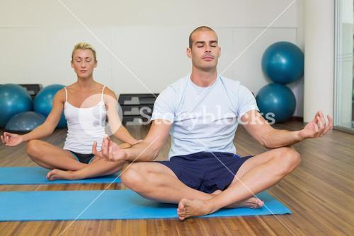 Couple sitting in lotus posture at fitness studio
