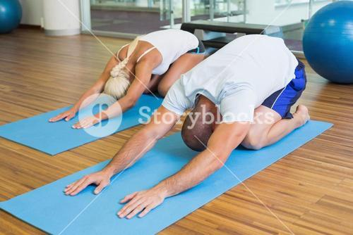 Couple in bending posture at fitness studio
