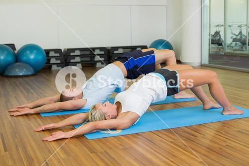 Couple doing pilate exercises at fitness studio