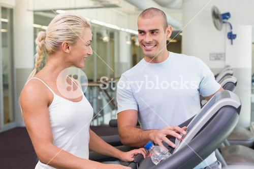 Trainer assisting woman with treadmill screen options at gym