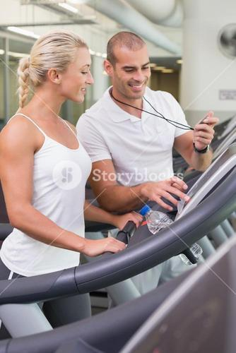 Male trainer timing his client on treadmill at gym