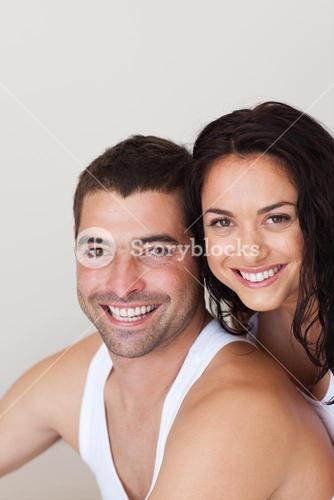 Positive young couple sitting on the bed