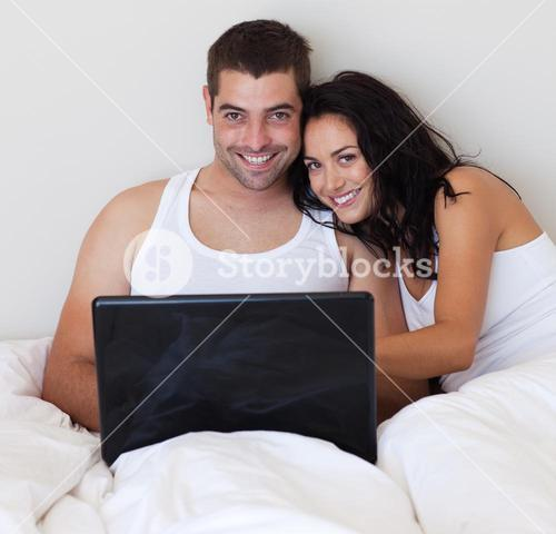 Jolly couple using a laptop at home