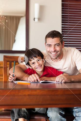 Little boy wearing a red shirt drawing pictures