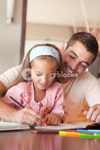 Concentrated girl painting with her father