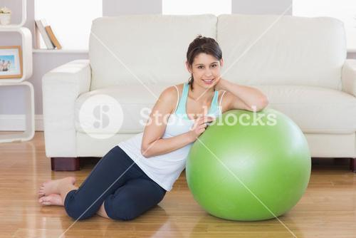 Fit brunette leaning on exercise ball smiling at camera