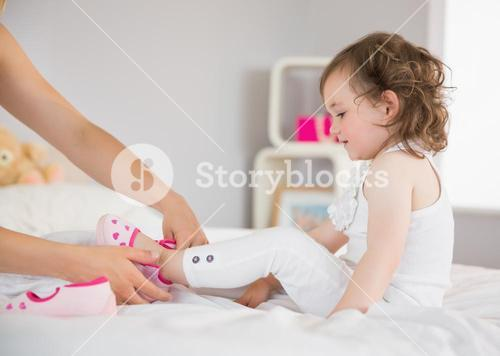 Mother dressing up daughter on bed
