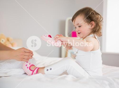 Mother dressing up young daughter on bed