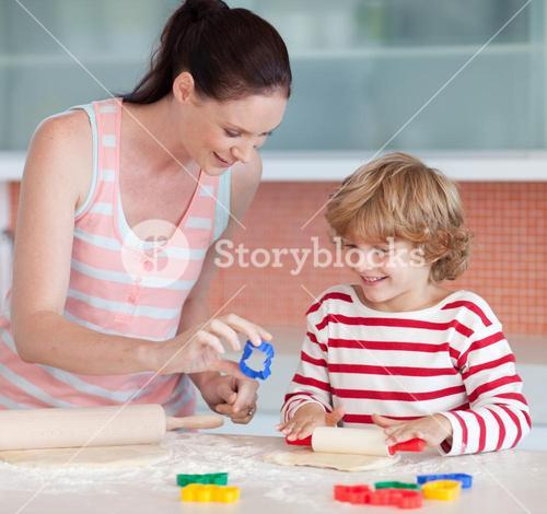 Smiling boy with his mother and cookie cutter
