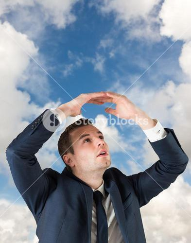 Composite image of businessman standing with hands over head