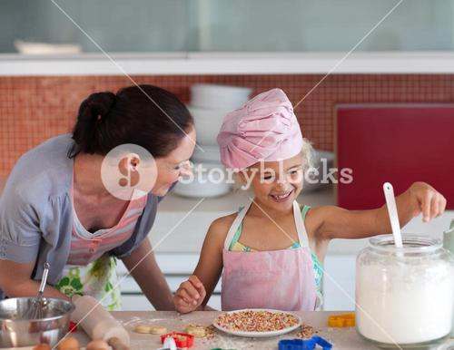 Young mother in kitchen teaching child