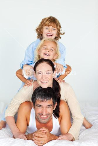 Parents and children playing together in bed