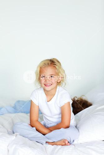 Little girl with brother on the bed