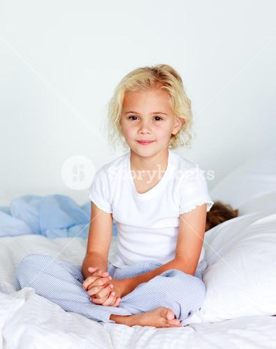Cute little blond girl sitting on her bed