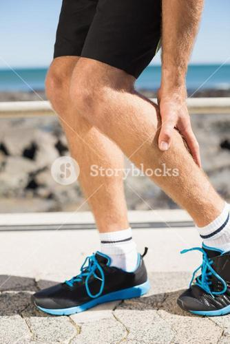 Fit man gripping his injured calf muscle