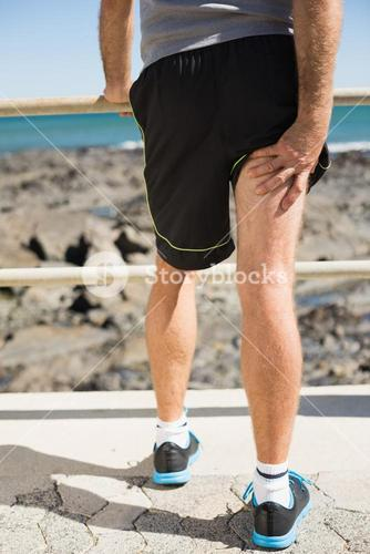 Fit man gripping his injured thigh