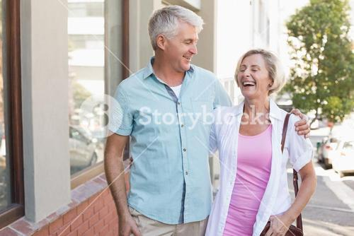 Happy mature couple walking in the city