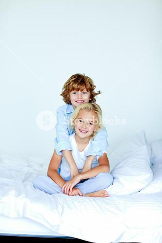Sister and brother embracing in bed