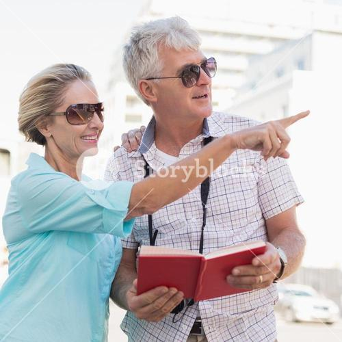 Happy tourist couple using tour guide book in the city
