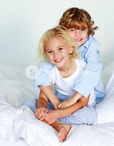 Little girl and boy on the bed