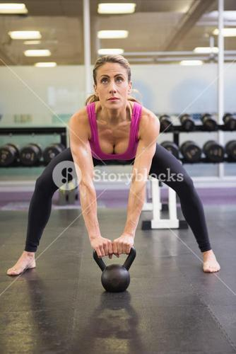 Full length of woman lifting kettle bell in gym