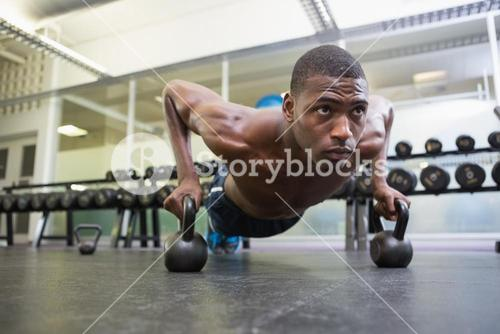 Determined man doing push ups with kettle bells in gym