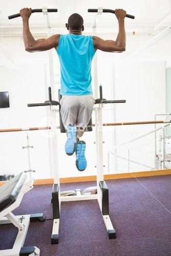 Rear view of muscular man doing pull ups at gym
