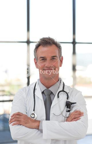 Smiling doctor with folded arms