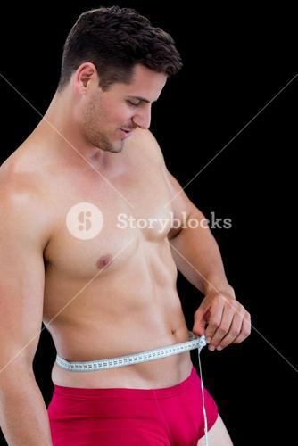 Side view of fit man measuring waist