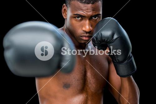 Young shirtless male boxer attacking with his right