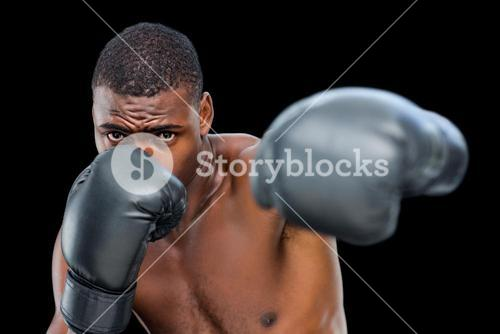 Young shirtless male boxer attacking with his left