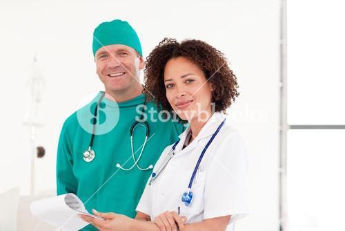 Surgeon and nurse smiling at the camera