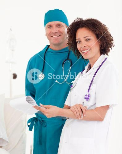 Friendly nurse with handsome surgeon in blue scrubs