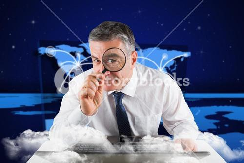 Composite image of mature businessman examining with magnifying glass