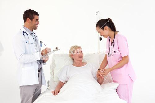 Smiling patient lying between friendly nurse and doctor