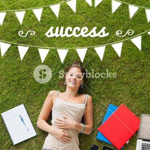 Success against pretty student lying on grass