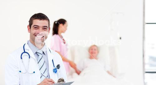 Delighted doctor holding a clip board