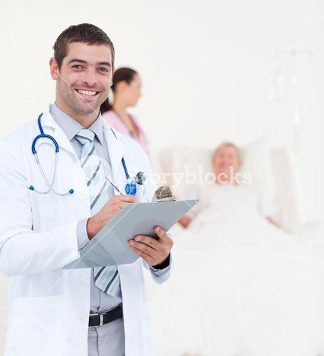 Successful male doctor writing on clip board