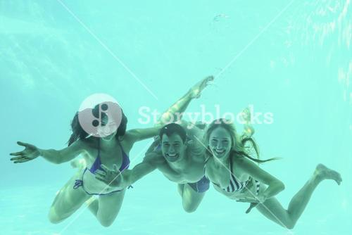 Friends underwater in swimming pool