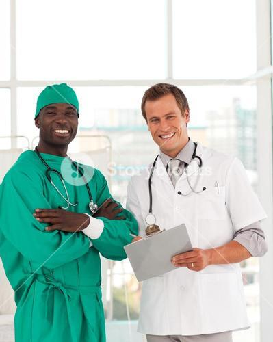 Surgeon and doctor smiling at camera