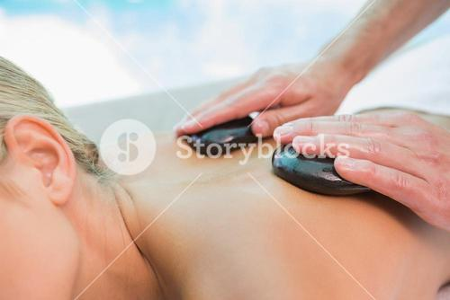 Mid section of woman receiving stone massage at health farm