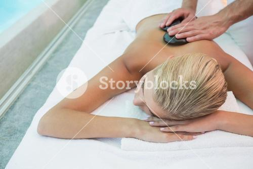 Woman receiving stone massage at health farm